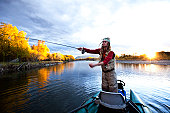 A fly fisher casting his line out of a boat while fly fishing surrounded by fall colors in Montana.