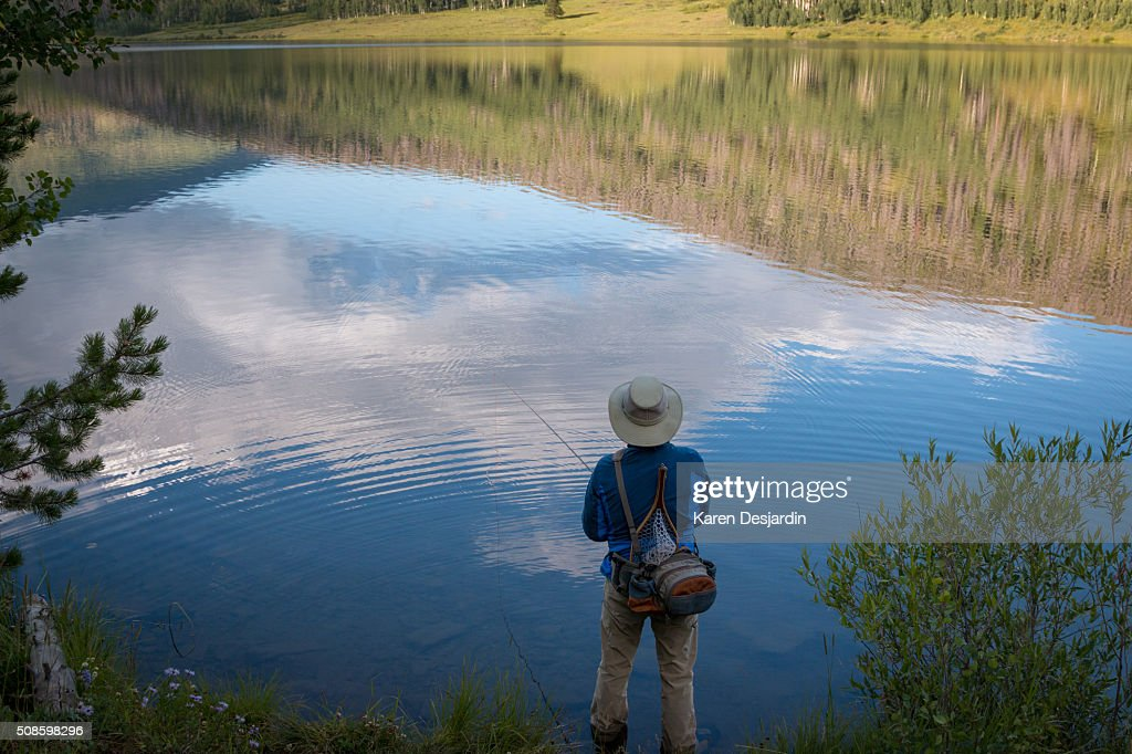 fly fisherman at mountain lake with reflections : Stock-Foto