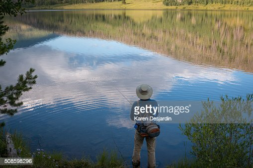 fly fisherman at mountain lake with reflections : Stock Photo