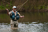 Fly fisherman casting a line in river