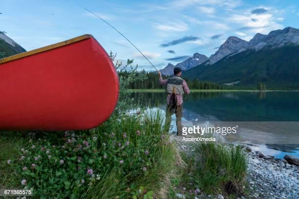 Fly fisherman casts line past canoe, mountain lake