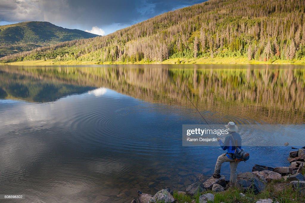 fly fisherman catching trout in mountain lake : Foto de stock