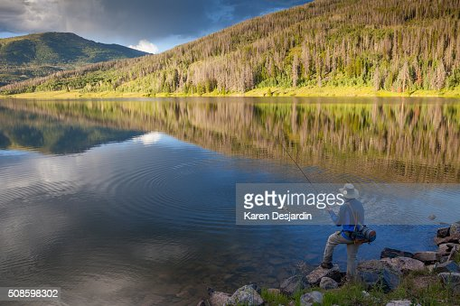 fly fisherman catching trout in mountain lake : Stock Photo