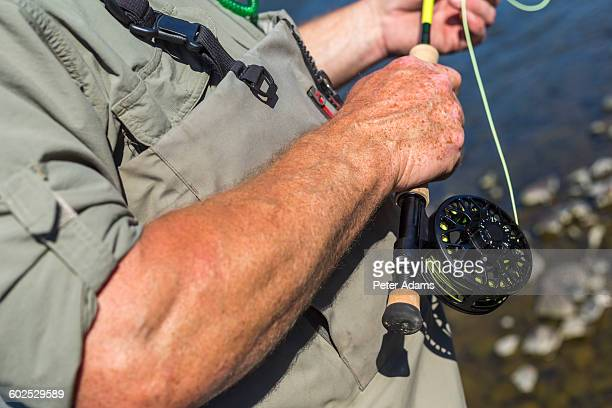 Fly fisherman fishing, close up of rod & reel
