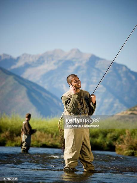 fly fisherman fishing in a mountain river