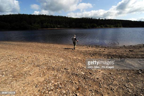 A fly fisherman has a longer than usual walk to the water's edge at Fewston Reservoir near Harrogate which has seen a fall in levels due to the dry...