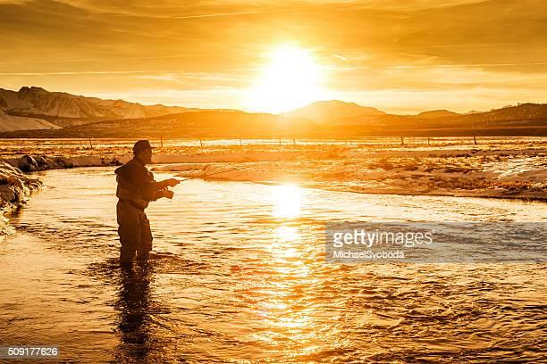 Mouche Pêcheur accès coince dans la rivière au coucher du soleil