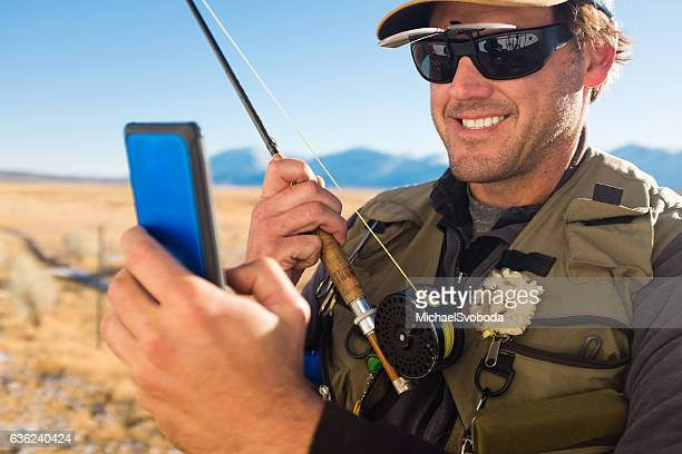 Fly Fisherman On His Cell Phone