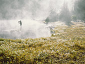Fly fisherman standing in lake covered with fog, casting, silhouette