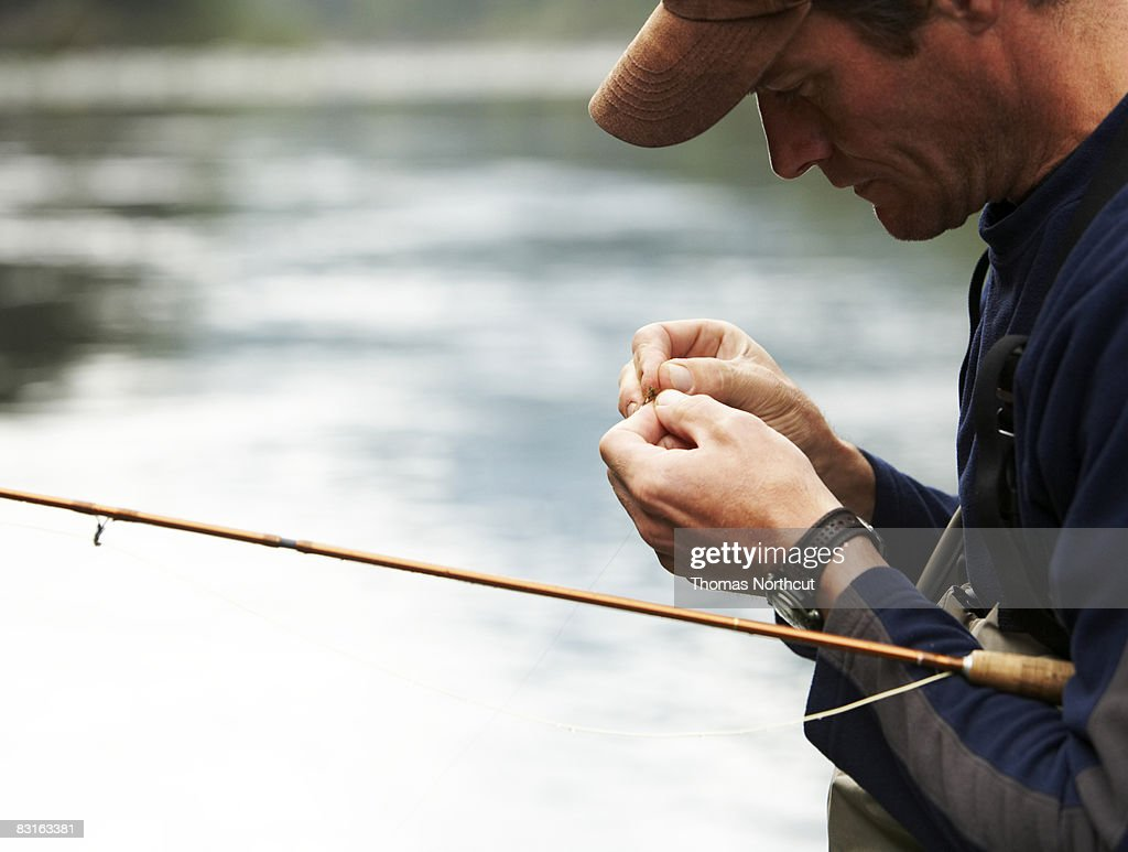 Fly fisherman tying lures : Stock Photo