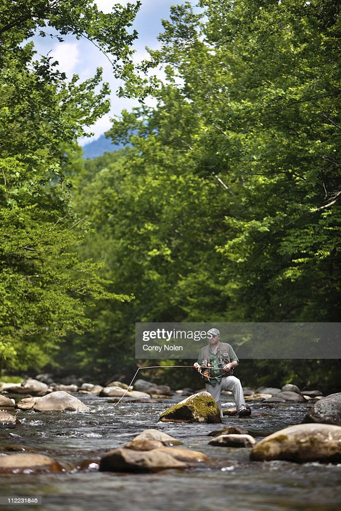 A fly fisherman watches the fly drift among large boulders in the Greenbrier River, Smoky Mountain National Park.