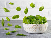 Flying fresh green basil leaves and bowl with spinach on gray table and white brick wall background. Fly spinach. Cooking pesto and raw food concept.
