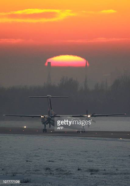 A Flybe aircraft takes off from the Belfast City Airport in Belfast Northern Ireland on December 23 2010 as the famous Harland and Wolff cranes are...