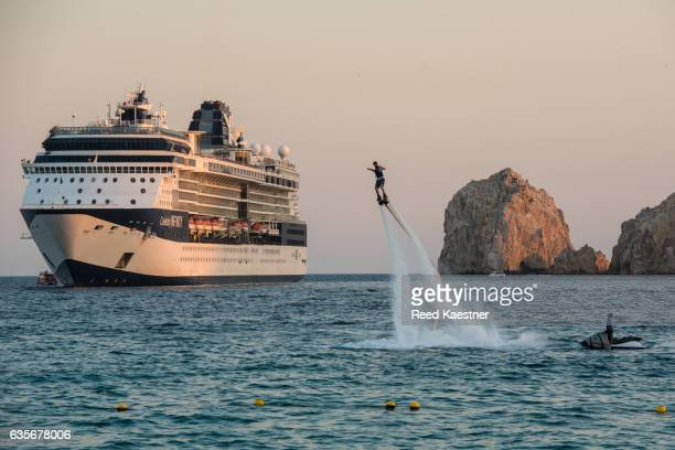 A flyboard rider takes to the air in Cabo San Lucas in front of an anchored cruise ship.