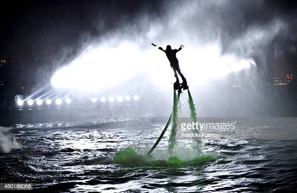 Flyboard riders flip in the air with a waterpropelled flyboard which connects to a personal water craft with a hose at the opening ceremony of...