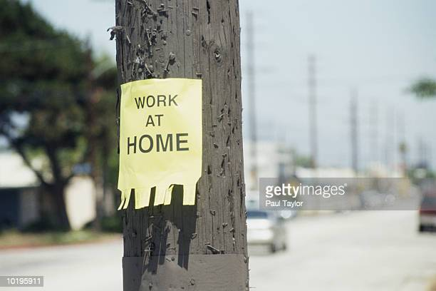 Flyer reading 'work at home', posted on telephone pole