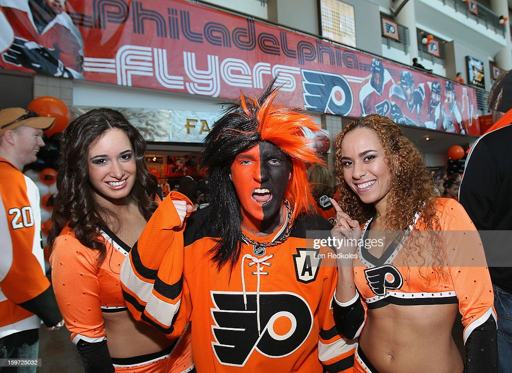 A Flyers fan and members of Philadelphia Flyers ice girls cheer on their team prior to playing the Pittsburgh Penguins on January 19, 2013 at the Wells Fargo Center in Philadelphia, Pennsylvania.