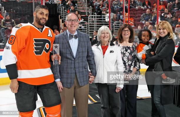Flyers Fan Club president Joe Fisher along with Sarah Hart Maureen Fisher and Lauren Hart present PierreEdouard Bellemare of the Philadelphia Flyers...