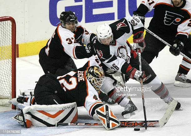 Flyers goalie Robert Esche makes a save against Sabres left winger Thomas Vanek as Flyers defenseman Eric Desjardins defends during Game 4 Eastern...