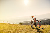 Grandfather flying a kite with his grandsons on mountain.They wear casual clothes and enjoy in great sunny day in nature.