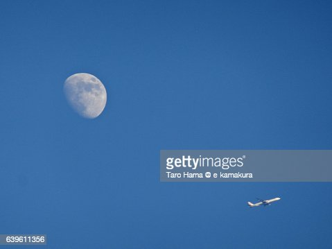 A flying airplane and moon in the sky