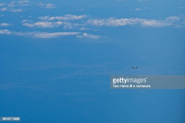 A flying airplane on clouds, daytime aerial view from airplane