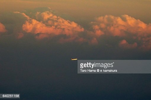 A flying airplane on sunset cloud