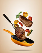 Flying beef steaks with grilled vegetable on pan. Concept of flying food. Separated on soft colored background. High resolution size