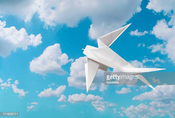 Flying blank origami Swallow against blue sky with copy space