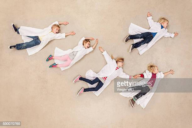 Flying children wearing laboratory coats