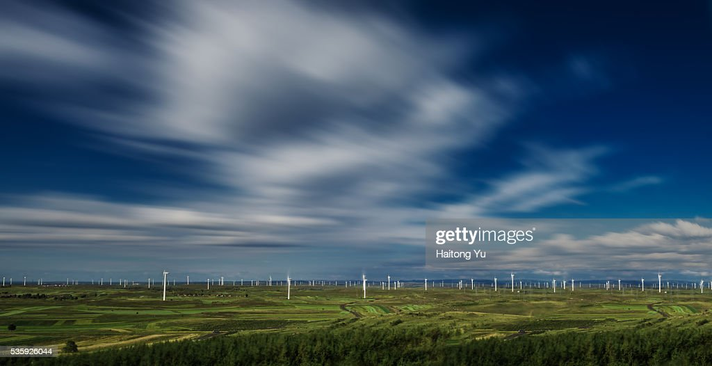 Flying clouds above wind farm : Stock Photo