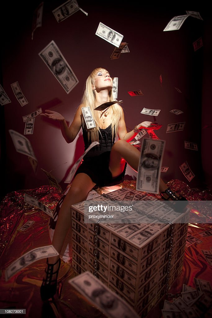 Flying dollars on beautiful blonde rich young woman : Stock Photo