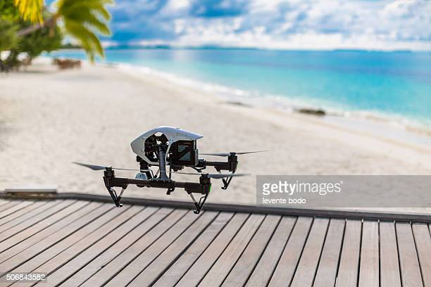 Flying drone with mounted camera on tropical beach