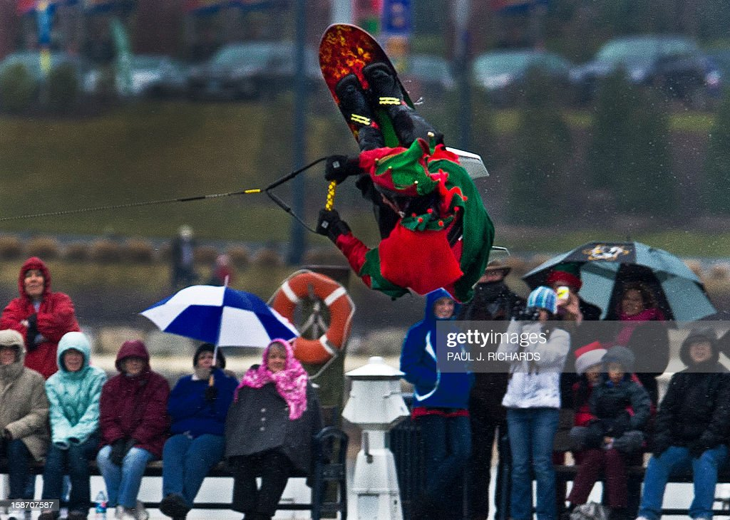 A flying Elf is seen doing a flip on a water ski chair as people look on during Christmas Eve performce on the Potomac River near Washington, DC, December 24, 2012, at National Harbor in Maryland. The free show is put on every Christmas Eve. AFP PHOTO/Paul J. Richards