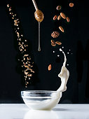 Falling granola with milk splash, falling nuts and honey flows from dipper. Healthy breakfast ingredients. Flying food