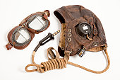 Elevated view of a C-Type leather flying helmet with bell jack & cable and a pair of Mark VIII flying goggles. These items were used by members of the Royal Air Force during World War Two. Studio shot