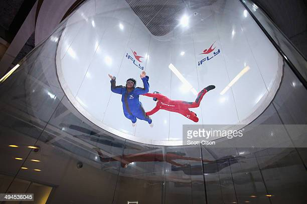 Flying instructor David Schnaible guides Patrece White as she learns wind tunnel flying at the iFly indoor skydiving facility on May 29 2014 in...