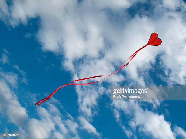 Flying kite in the shape of a red heart against the blue sky