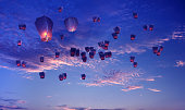 Large group of Chinese lanterns flying over blue sky background