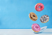 Flying multicolored donuts with plate on a blue background. toning. selective focus