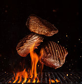 Flying pieces of beef rump steaks above grill flames, isolated on black background. Concept of flying food, very high resolution image