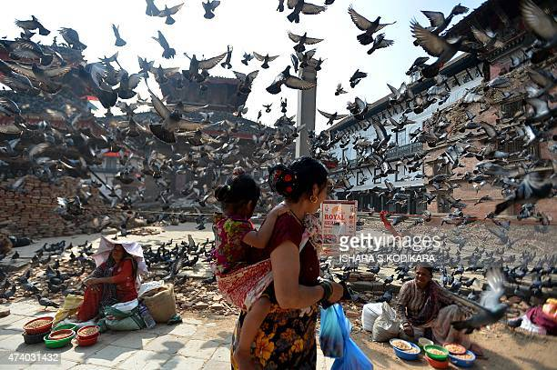 Flying pigeons pass over Nepalese street vendors near the earthquake damaged UNESCO World Heritage Site Durbar Square in Kathmandu on May 20 2015...