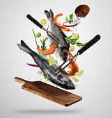Flying raw whole bream fish and prawns, with ingredients for cooking. Freeze motion of cooking staff. Fork holding the meat. Concept of food preparation in low gravity mode. Separated on smooth gray b