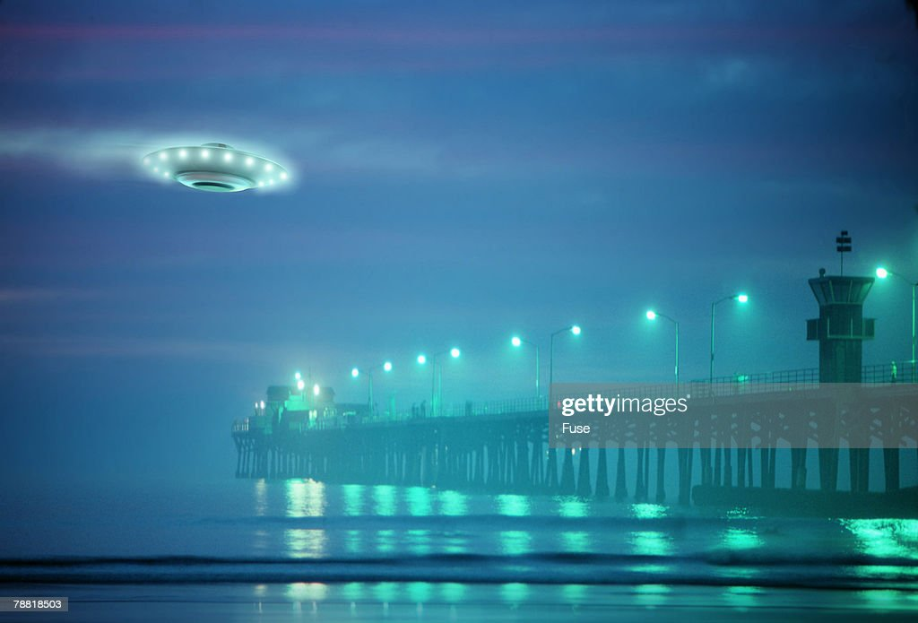 Flying Saucer near a Pier at Twilight : Stock Photo