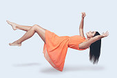 Full length studio shot of attractive young woman in orange dress hovering in air and keeping eyes closed