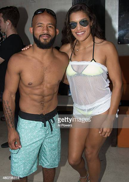 UFC flyweight champion Demetrious Johnson and strawweight Juliana Pena pose for a photo during a UFC pool party as part of the International Fight...