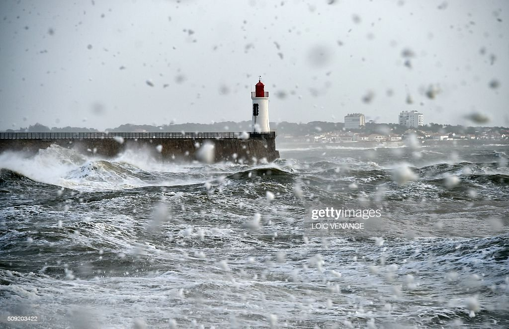 Foam flies as a wave breaks against a pier in Les Sables-d'Olonne, western France, on February 9, 2016. High winds buffeted northwestern Europe on February 8, leaving one woman in France in a coma after she was hit by an advertising hoarding. Electricity was cut to 5,000 homes in northern France. / AFP / LOIC VENANCE
