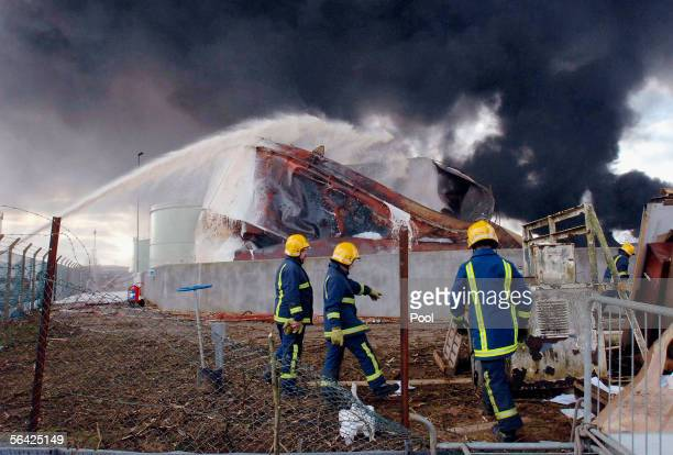 Foam is sprayed on one of the fuel storage tanks at Buncefield oil depot as the fires continue to burn for a third day on December 13 2005 in Hemel...