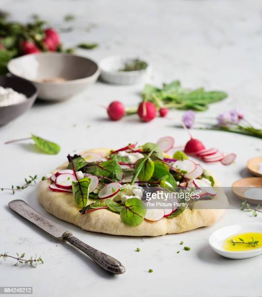 Focaccia bread with fresh salad and raw vegetable on marble table