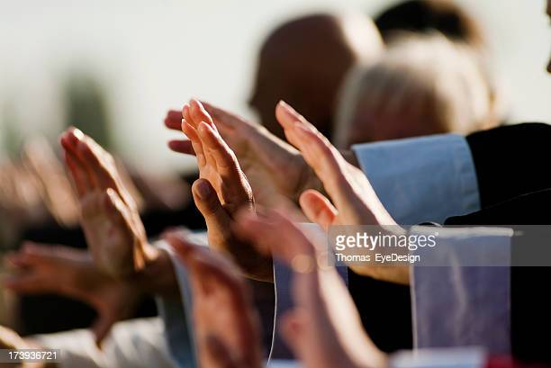Focus on a group of people's hands performing Tai Chi moves